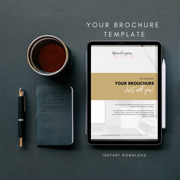 The Interior Designers Club Your Brochure Template on a dark grey background, viewed on a tablet screen, next to a coffee, notebook and pen